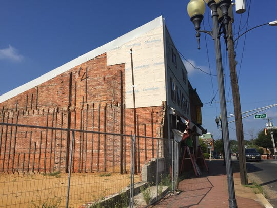 The eastern wall of Jim's Lunch restaurant , now fenced off, was damaged during demolition this year of the adjacent Eagles building at 109 E. Main Street. The city plans to open bids bids on Sept. 13 from contractors interested in repairing the damage. In this photo, from Thursday, workers are removing an awning from in front of the restaurant.