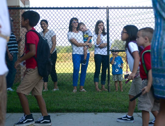 Parents catch a glimpse of their children at Petway Elementary School on the first day of school on Thursday, September 6.