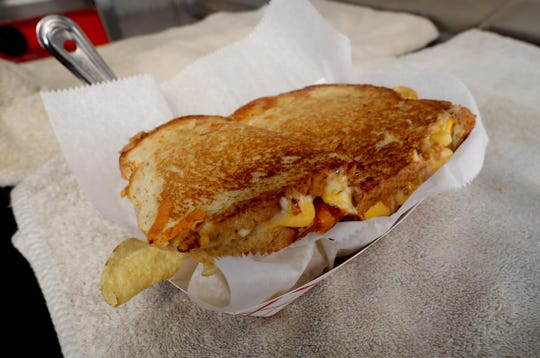 """A grilled cheese sandwich called the """"Liam 2.0, prepared by Lyle Buente, the owner of Put Some Meat on Your Bones, a food truck located outside the Jefferson Valley Mall in Yorktown Heights, photographed Sept. 6, 2018. The sandwich features a six cheese blend, barbecue chicken, turkey chipotle chile, and macaroni and cheese."""