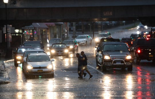 Pedestrians scramble across Westchester Avenue in Port Chester during an early evening thunder shower Sept. 6, 2018.