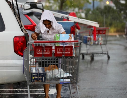 Gloria Gomez of Port Chester had only a towel to protect her from the rain as she loaded her car with groceries after shopping in Costco in Port Chester during the early evening thunderstorm Sept. 6, 2018.