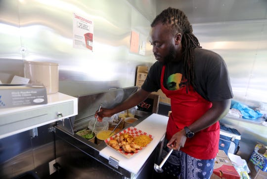 Chef Lawrence Ofori, owner of Spicy, a food truck located outside the Jefferson Valley Mall in Yorktown Heights, prepares a dish Sept. 6, 2018. Ofori specializes in chicken wings and different types of fish, all prepared with his homemade sauces.