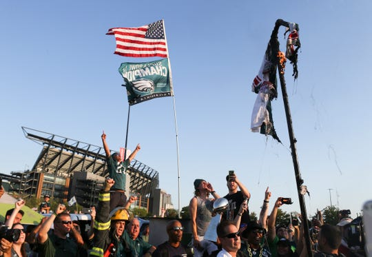 "A jersey mocking the Eagles' ""0 Superbowls"" smolders after it was torched as fans gather for tailgating at Lincoln Financial Field before the season opener against Atlanta Thursday."