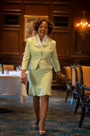 Sheila Marlowe wears a Tahari mint-green suit with fitted jacket, rosebud buttons and kick-pleats; white Calvin Klein blouse; and beige, sling-back patent leather Ellen Tracy pumps.
