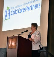 Board chair Jeanmarie Baer unveils the new name and logo of Child Care Inc., which is now Child Care Partners, during an anniversary luncheon marking 100 years for the organization. The event was held at The Forum.