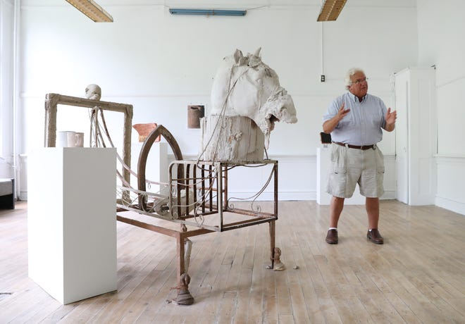 David Mitzel, owner of Pioneer School Zanesville Clay Center, talks about the center's mission next to a piece by Toledo clay artist Eric Zohn