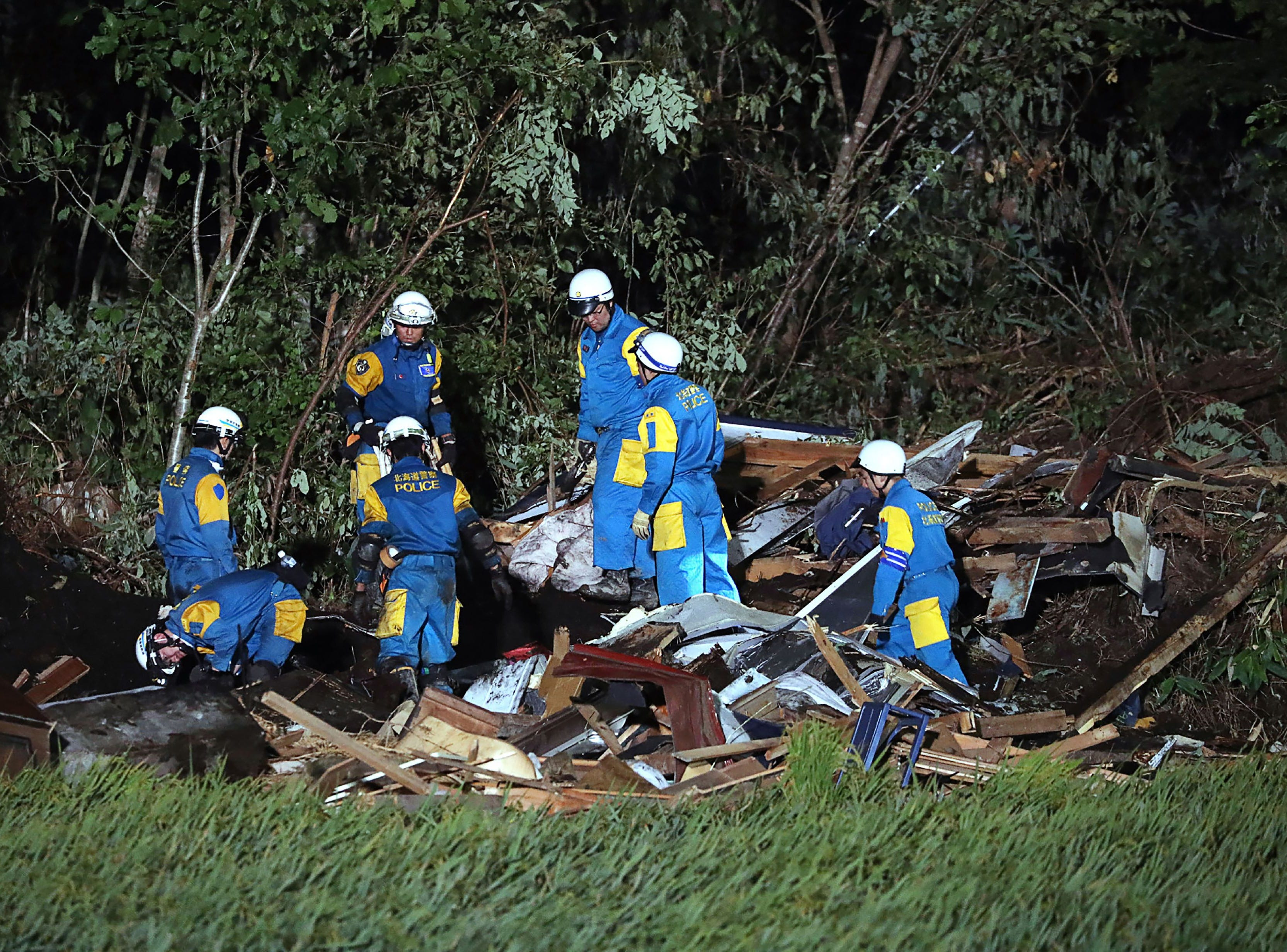 Japanese policemen work during a rescue operation in the area affected by landslides triggered by an earthquake in Atsuma, Hokkaido prefecture on Sept. 6, 2018.