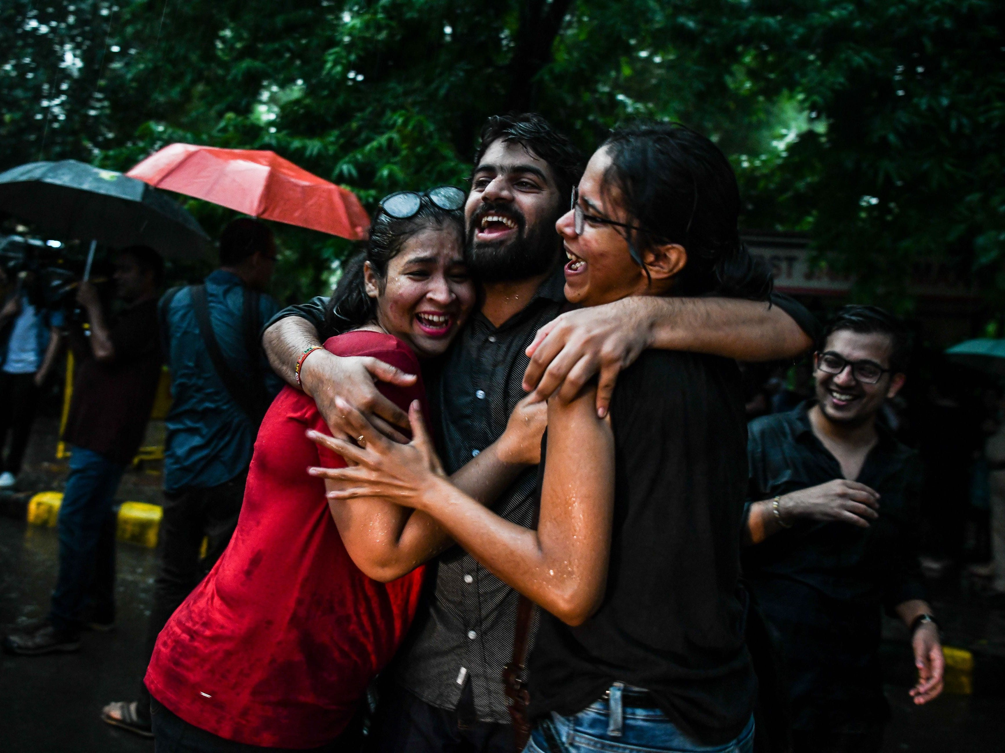 Gay rights supporters celebrate the Supreme Court decision to strike down a colonial-era ban on gay sex, during heavy rainfall in New Delhi, Sept. 6, 2018.