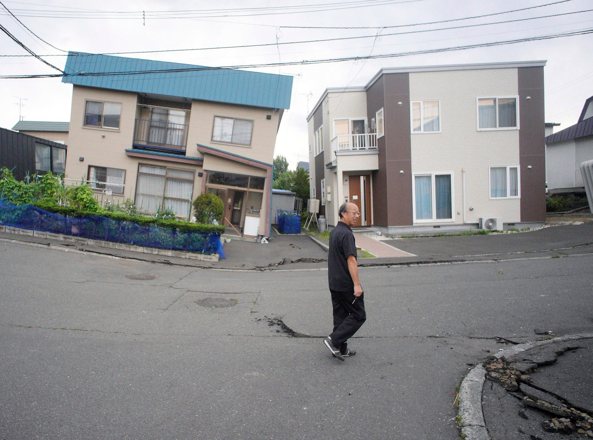 A resident walks by damaged houses in Kiyota, outskirts of Sapporo city, Hokkaido, northern Japan, Friday, Sept. 7, 2018.