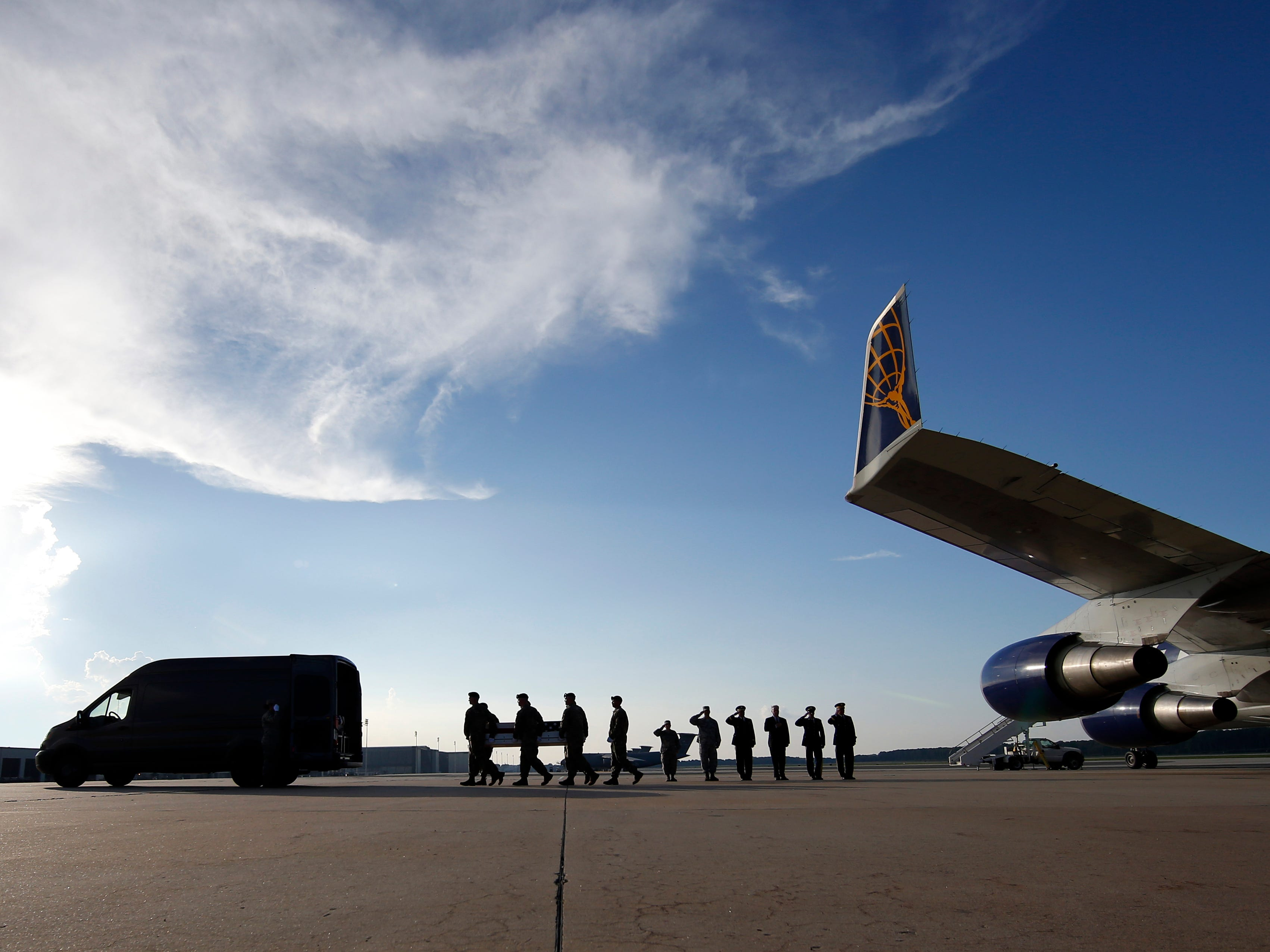 An Army carry team moves a transfer case containing the remains of U.S. Army Staff Sgt. Diobanjo S. San Agustin as members of the Official Party salute at Dover Air Force Base.