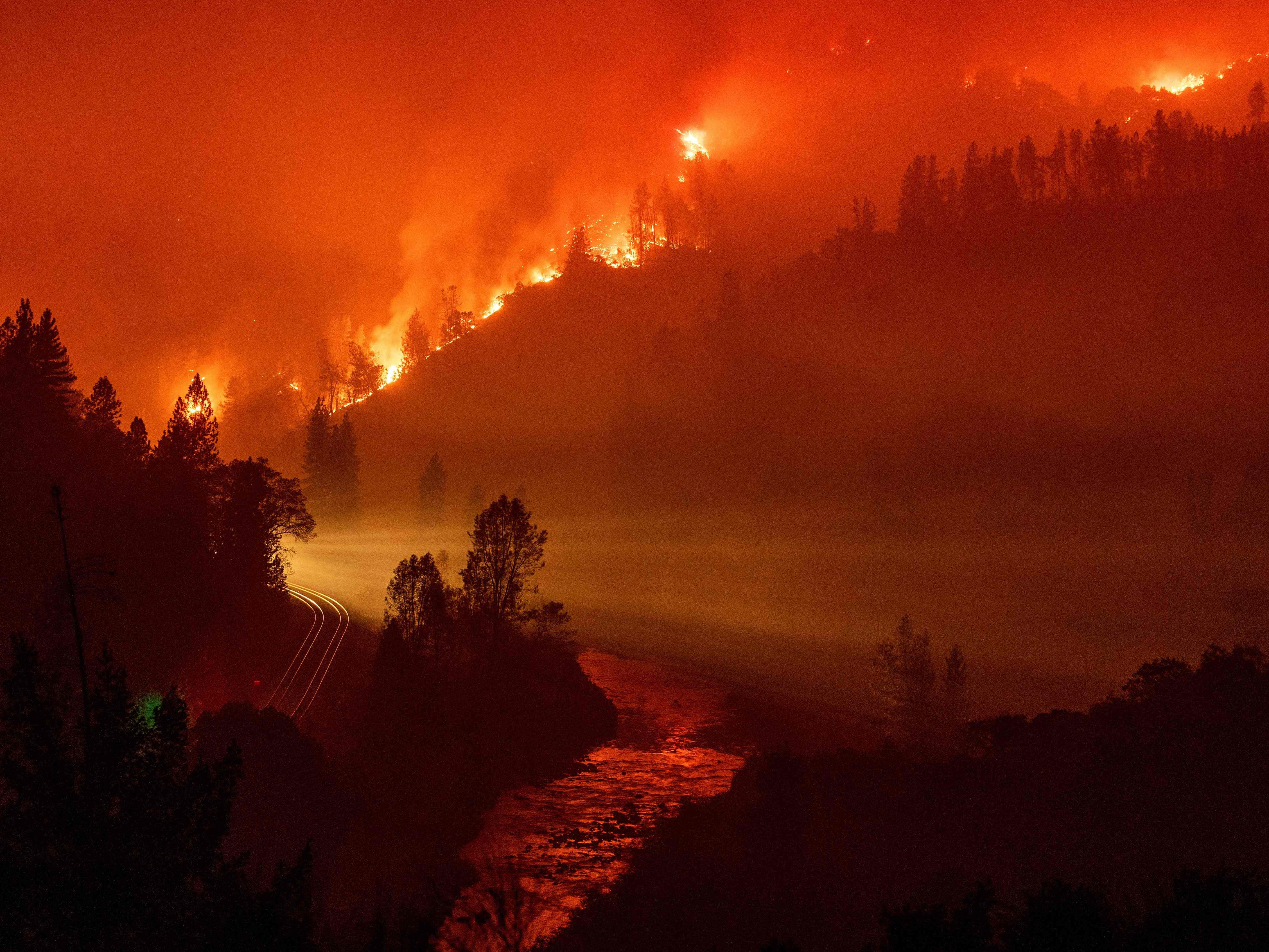 Light from a train is seen as it rounds a bend near the Sacramento River as flames from the Delta Fire fill a valley in Delta, Calif. on September 6, 2018.