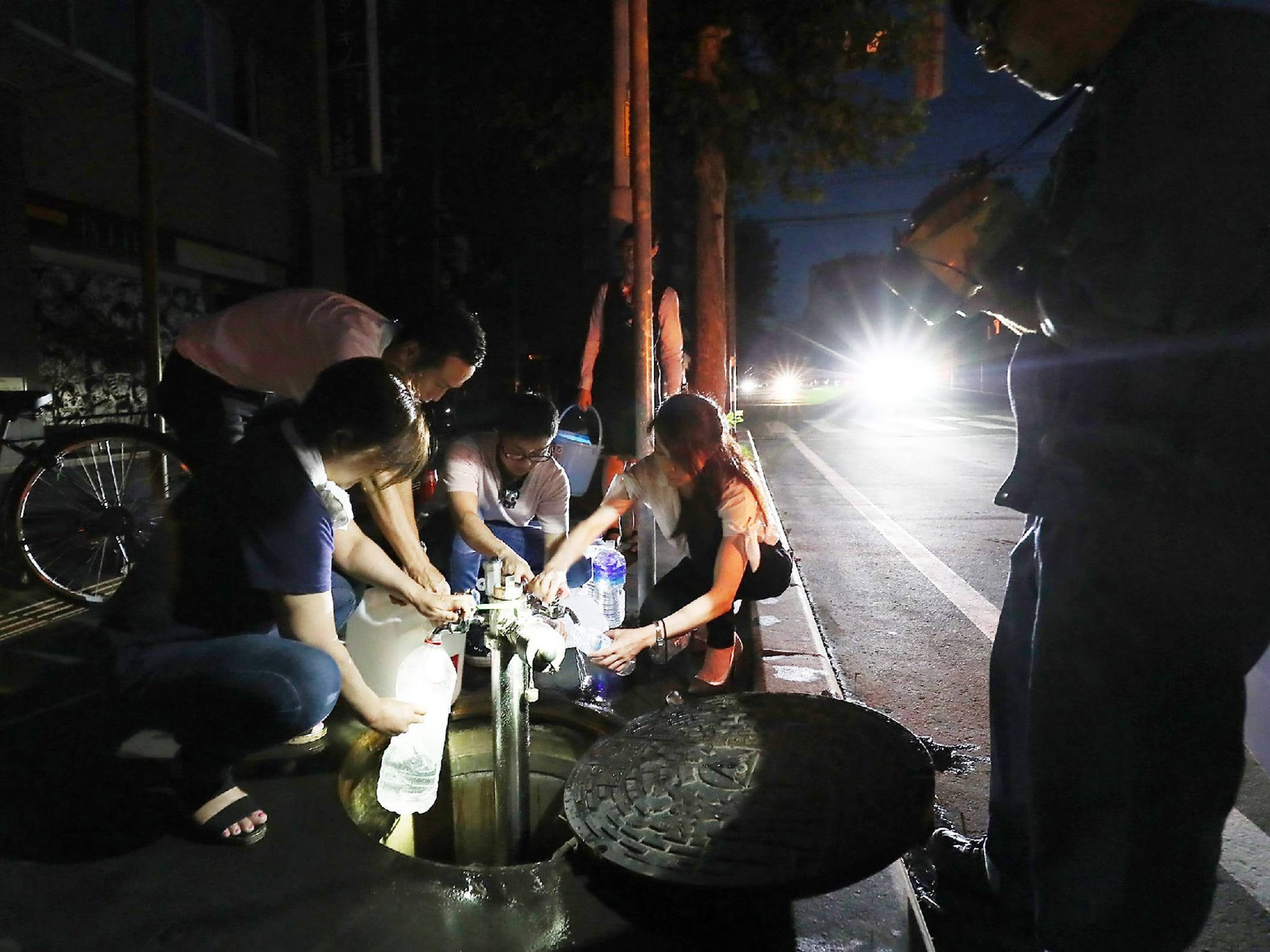 Earthquake-affected residents fill water bottles as an electrical blackout shrouds the shopping district in Sapporo, Japan on Sept. 6, 2018.
