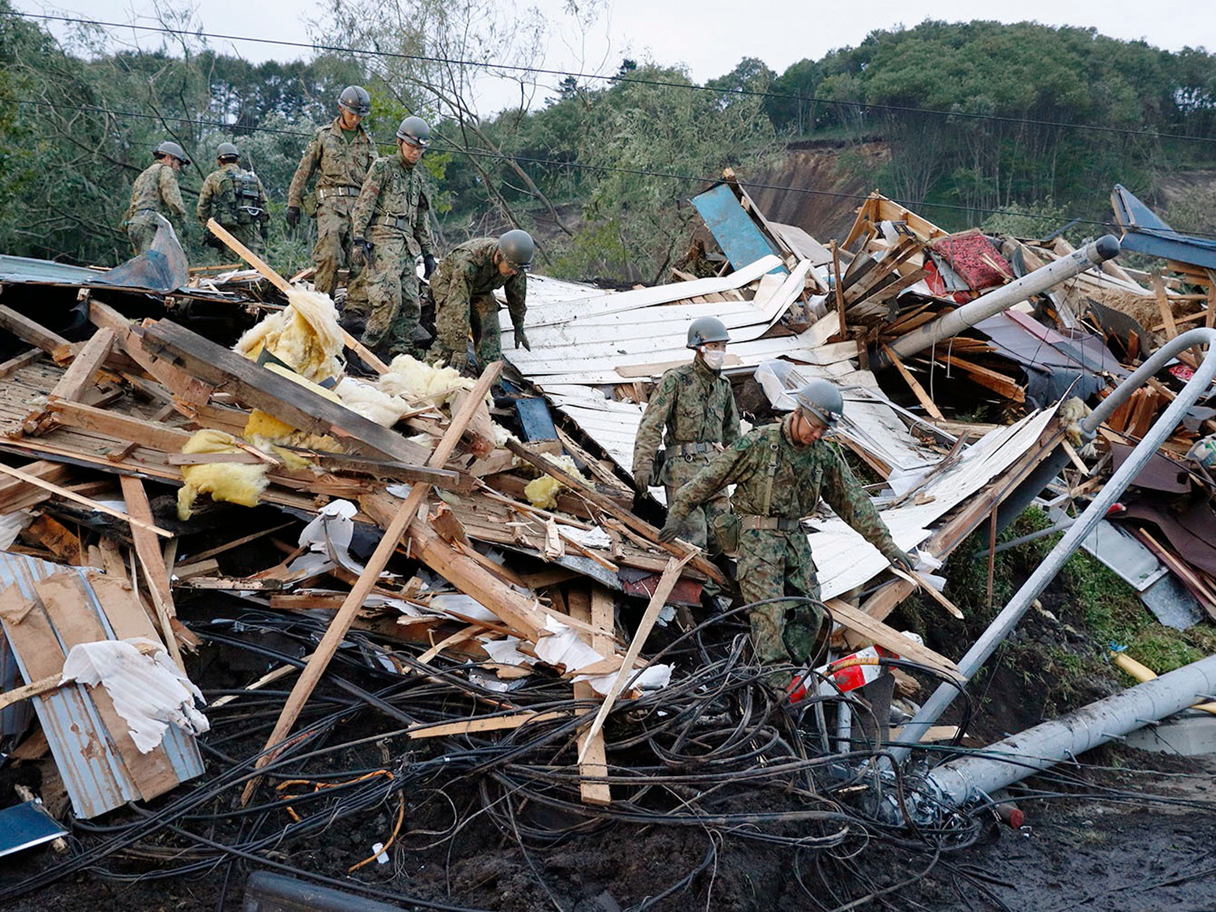 Japan Ground Self-Defense Force personnel shift through debris as they search for missing persons at the site of a landslide triggered by a powerful earthquake in Atsuma, Hokkaido, northern Japan, Friday, Sept. 7, 2018. A powerful earthquake Thursday on Japan's northernmost main island of Hokkaido triggered dozens of landslides that crushed houses under torrents of dirt, rocks and timber, prompting frantic efforts to unearth any survivors.