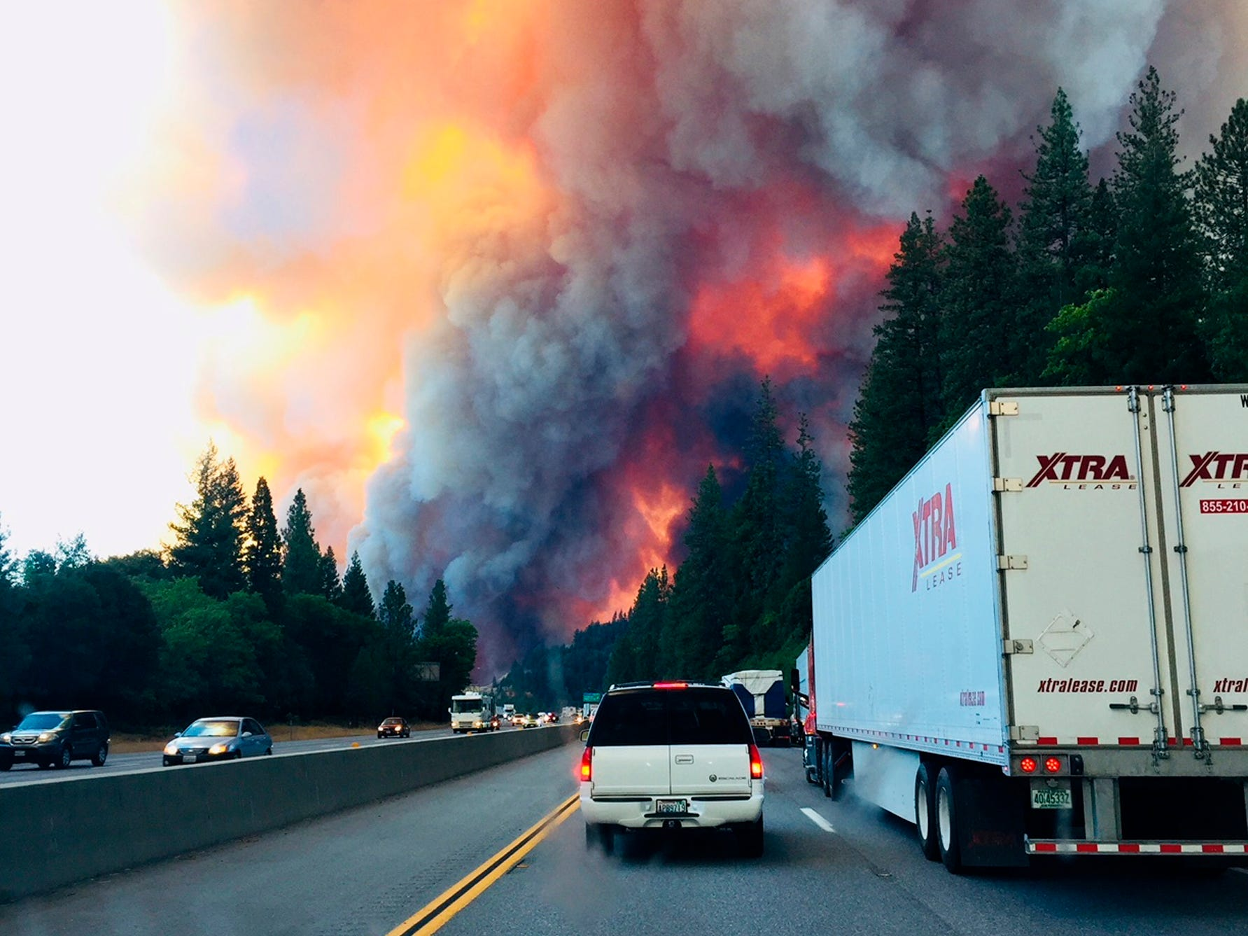 A fire rages as motorists travel on Interstate 5 near Lake Shasta, Calif., Sept. 5, 2018.