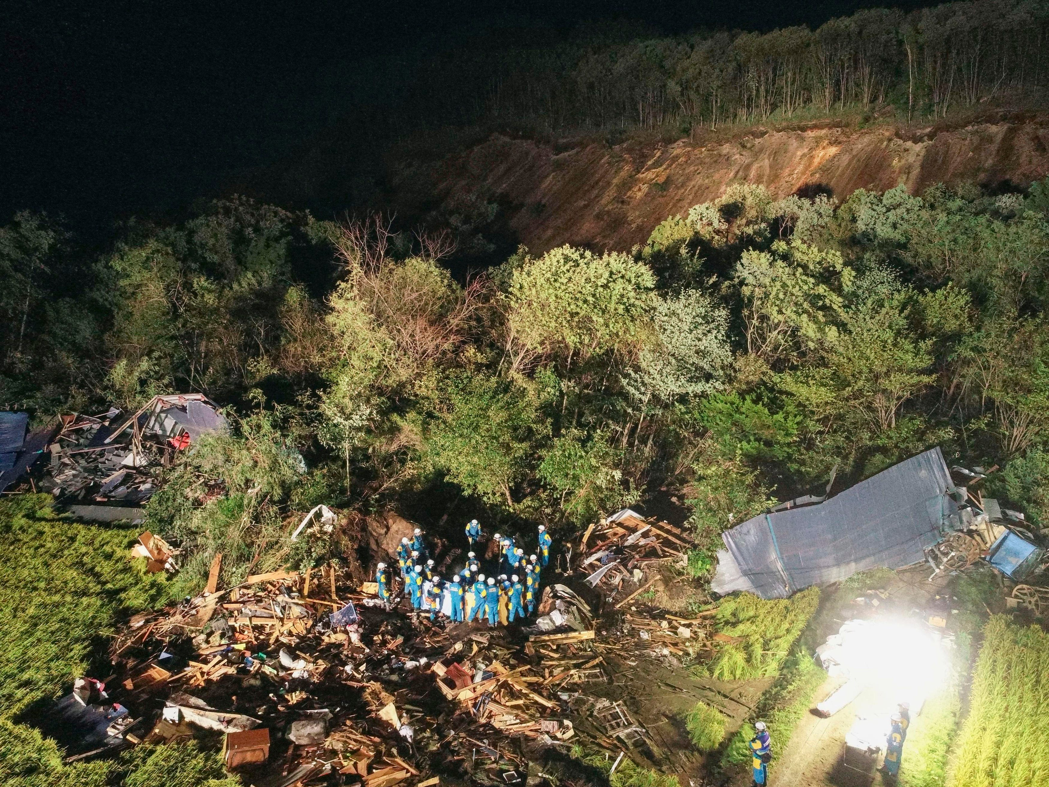Rescuers work around collapsed buildings due to landslides in Atsuma, Hokkaido, northern Japan Thursday, Sept. 6, 2018.