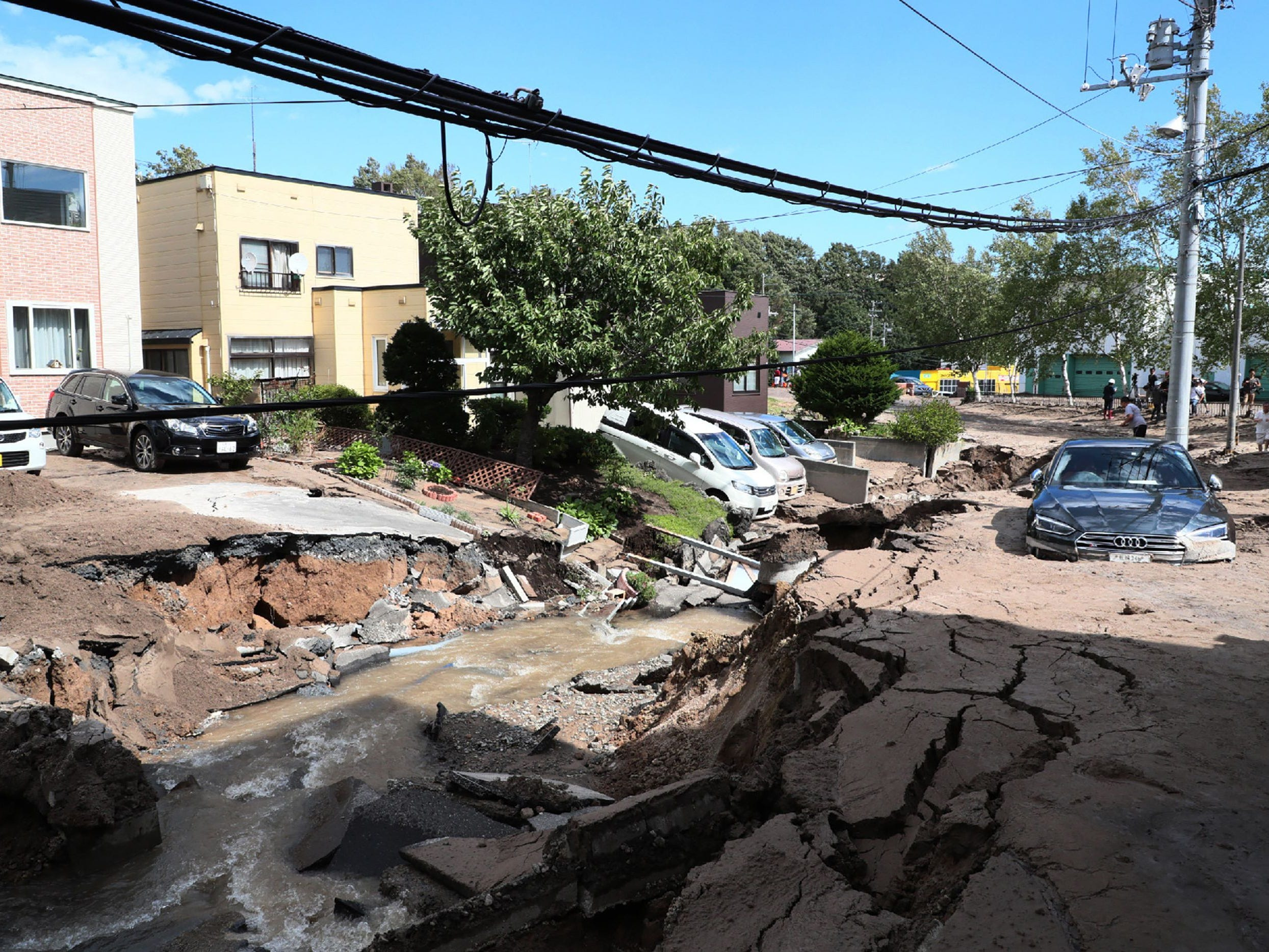 A car is stuck on a road damaged by an earthquake in Sapporo, Hokkaido prefecture on Sept. 6, 2018.
