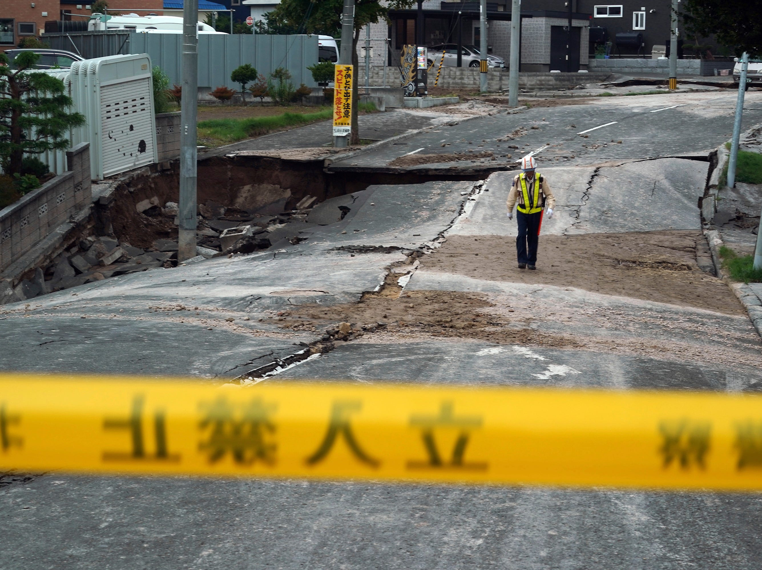 A security guard walks on an earthquake-damaged street in Kiyota, outskirts of Sapporo city, Hokkaido, northern Japan, Friday, Sept. 7, 2018.