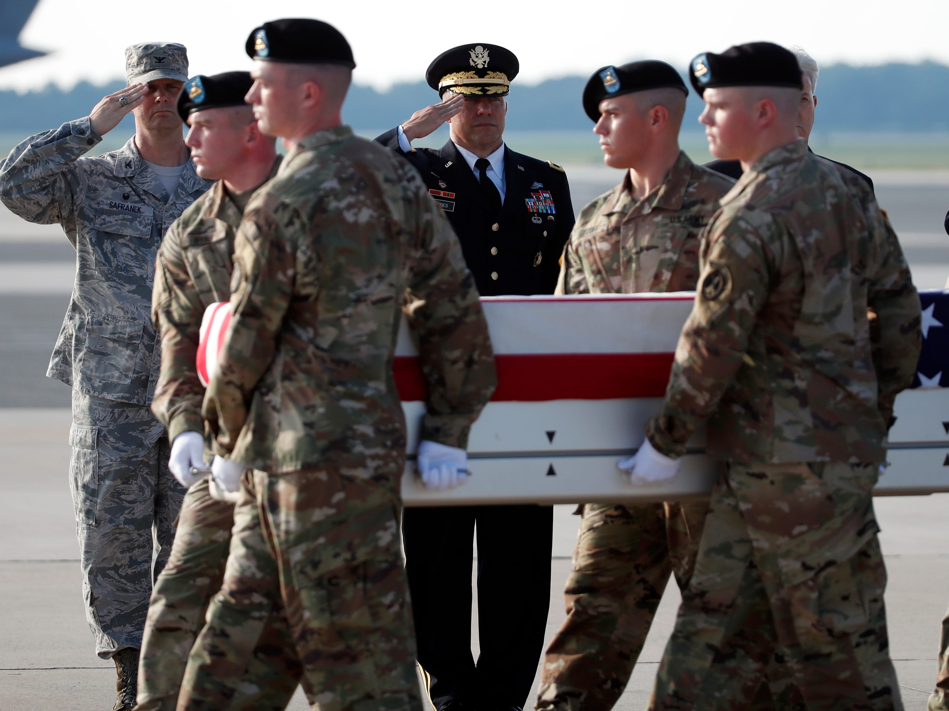 An Army carry team moves a transfer case containing the remains of U.S. Army Staff Sgt. Diobanjo S. San Agustin as Col. Joel W. Safranek, 436th Air Lift Wing Commander, left, and Brig. Gen. Mark Landes, Director of the Security Forces Directorate, salute at Dover Air Force Base.