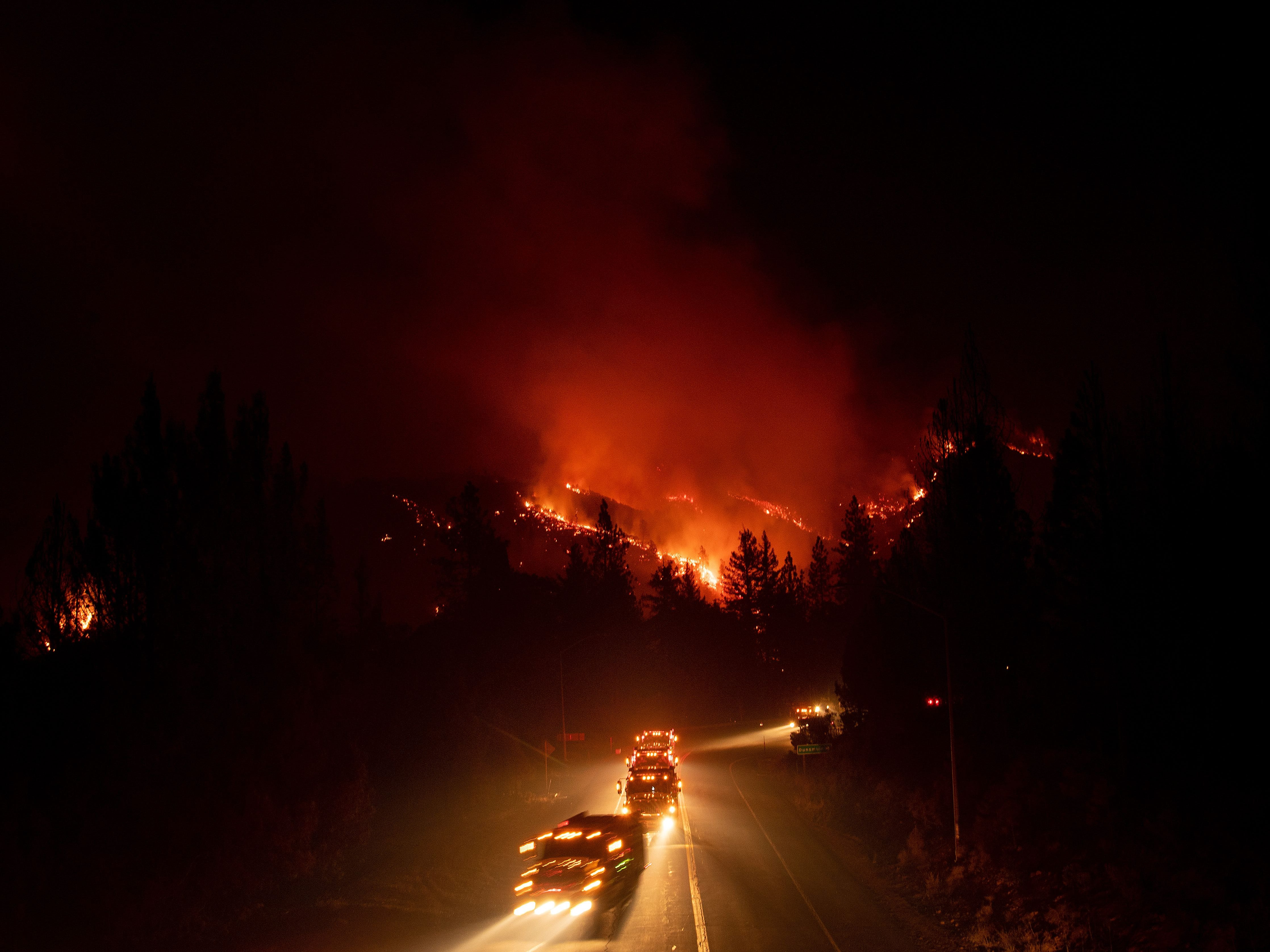 Fire trucks drive away from a burning hillside during the Delta Fire in Delta, Calif. on September 5, 2018.
