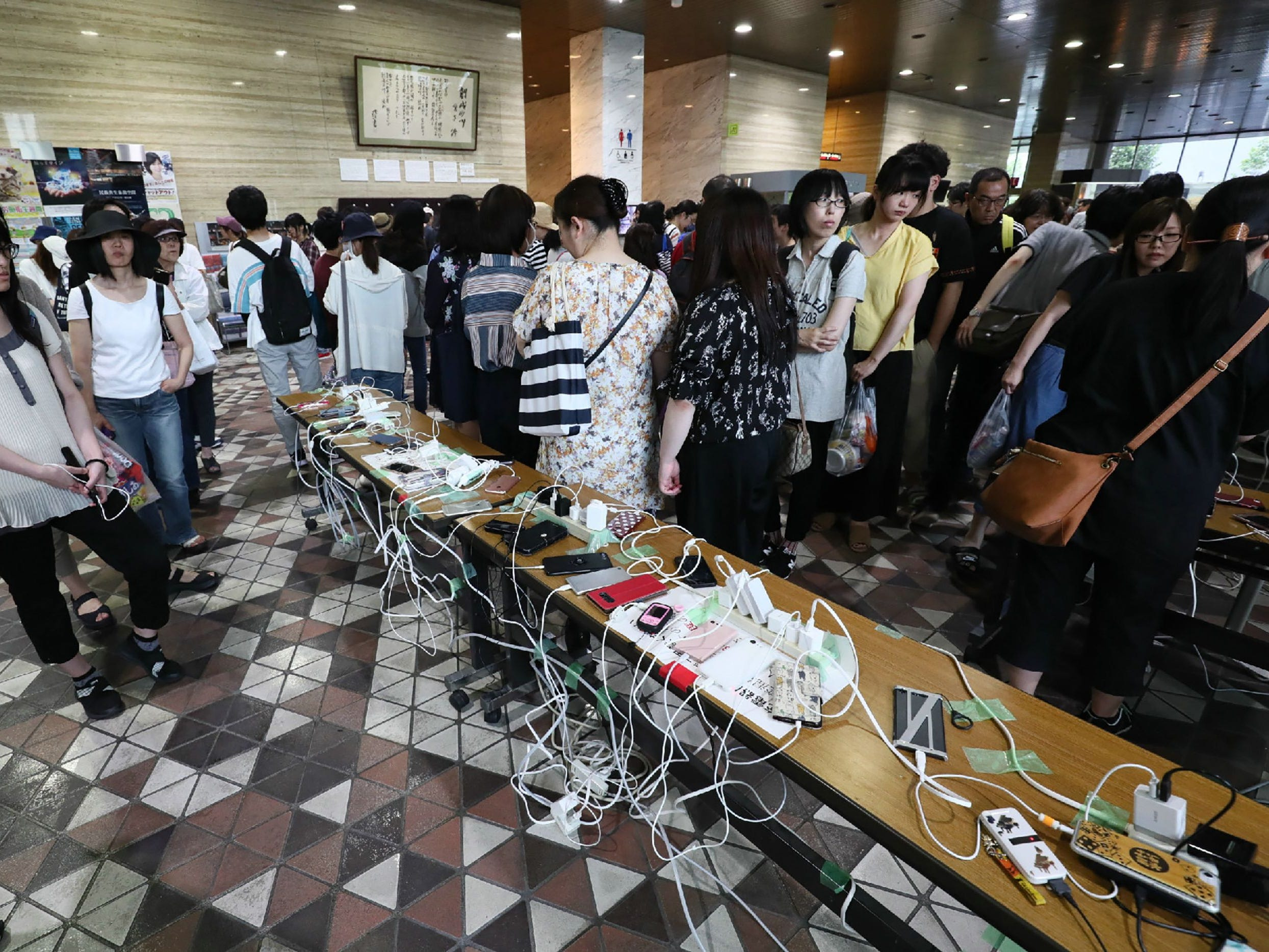 Residents charge their mobile phones at the Hokkaido prefectural headquarters in Sapporo, Hokkaido prefecture on Sept. 6, 2018, due to a blackout after an earthquake hit the northern Japanese island of Hokkaido.