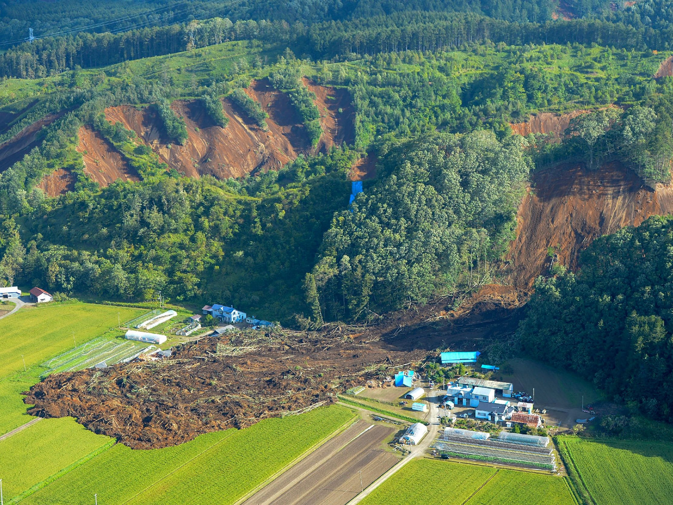 This picture shows an aerial view of houses damaged by a landslide in Atsuma town, Hokkaido prefecture on Sept. 6, 2018, after an earthquake hit the northern Japanese island of Hokkaido.