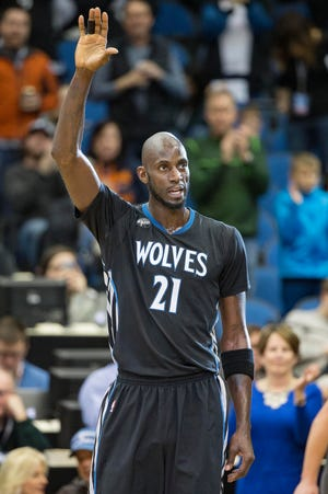 Minnesota Timberwolves forward Kevin Garnett waves to fans during a stoppage in play.