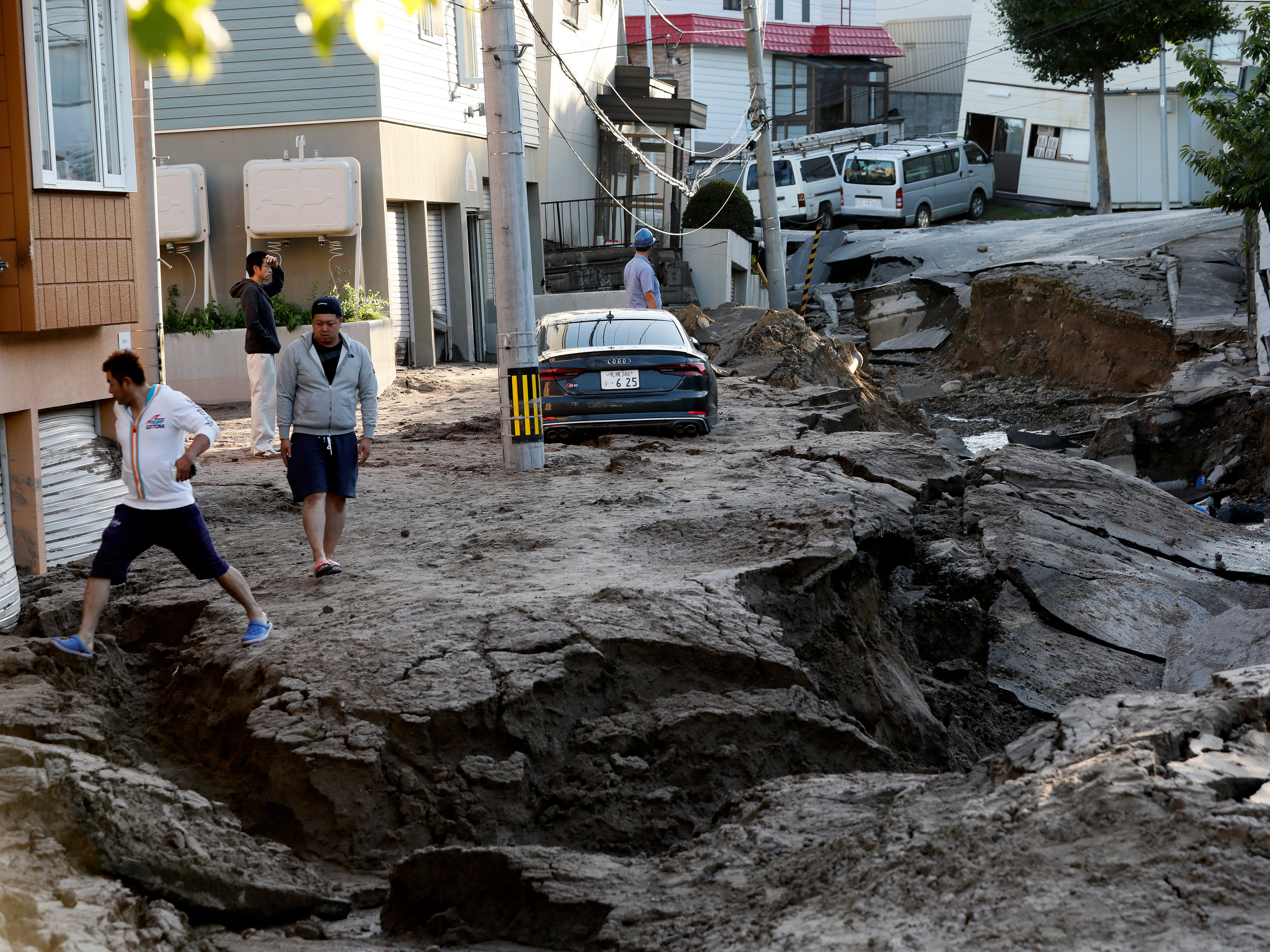 A resident leaps over a crack of a severely damaged road following a powerful earthquake in Sapporo, Hokkaido, northern Japan, Sept. 6, 2018. The Japan Meteorological Agency said a magnitude 6.7 earthquake jolted Japan's northern island of Hokkaido in the early hours of Sept. 6, killing at least seven people, injuring hundreds and causing large landslides and blackouts, affecting almost three million households.