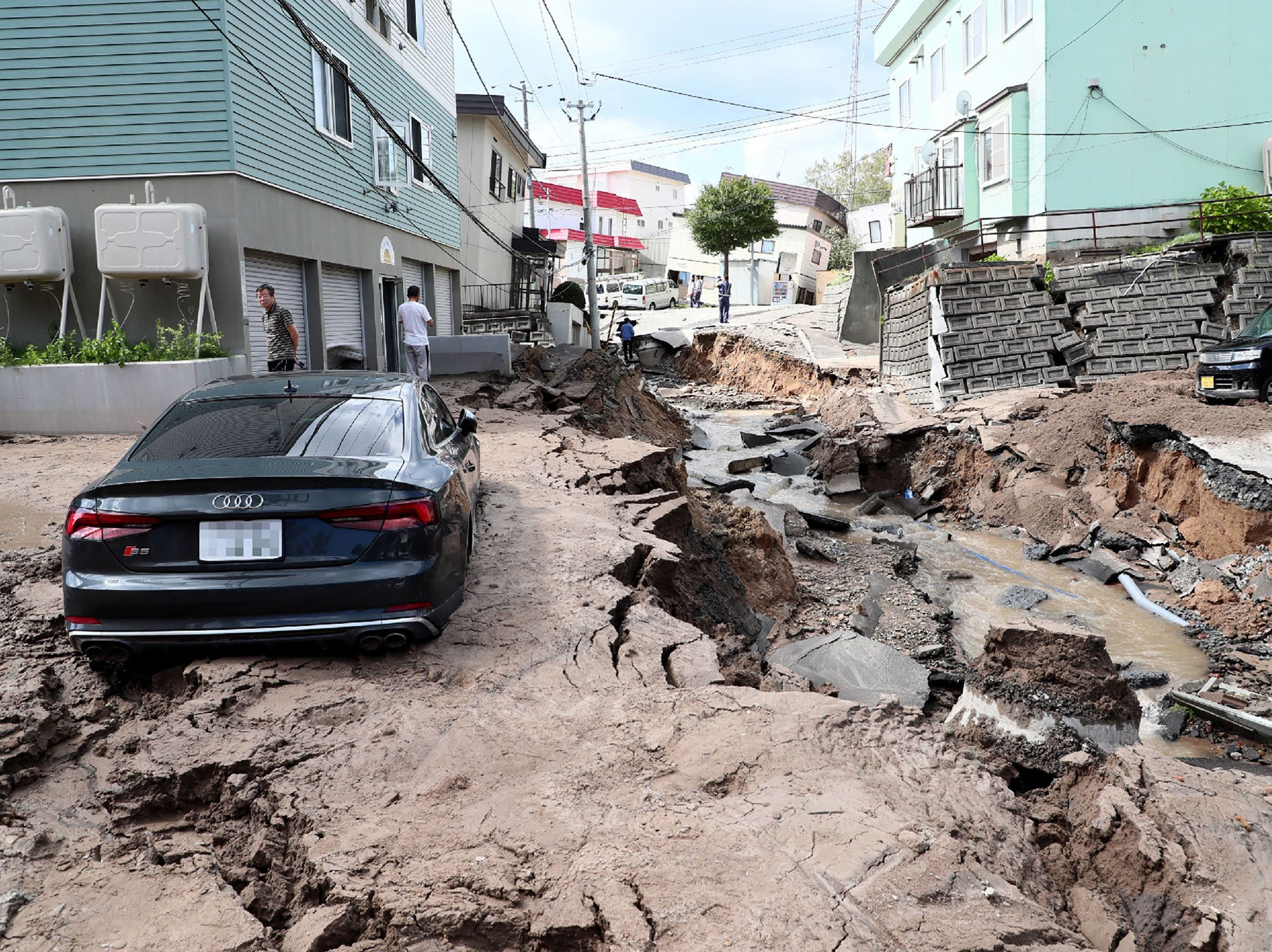 A car is seen stuck on a road damaged by an earthquake in Sapporo, Hokkaido prefecture on Sept. 6, 2018.