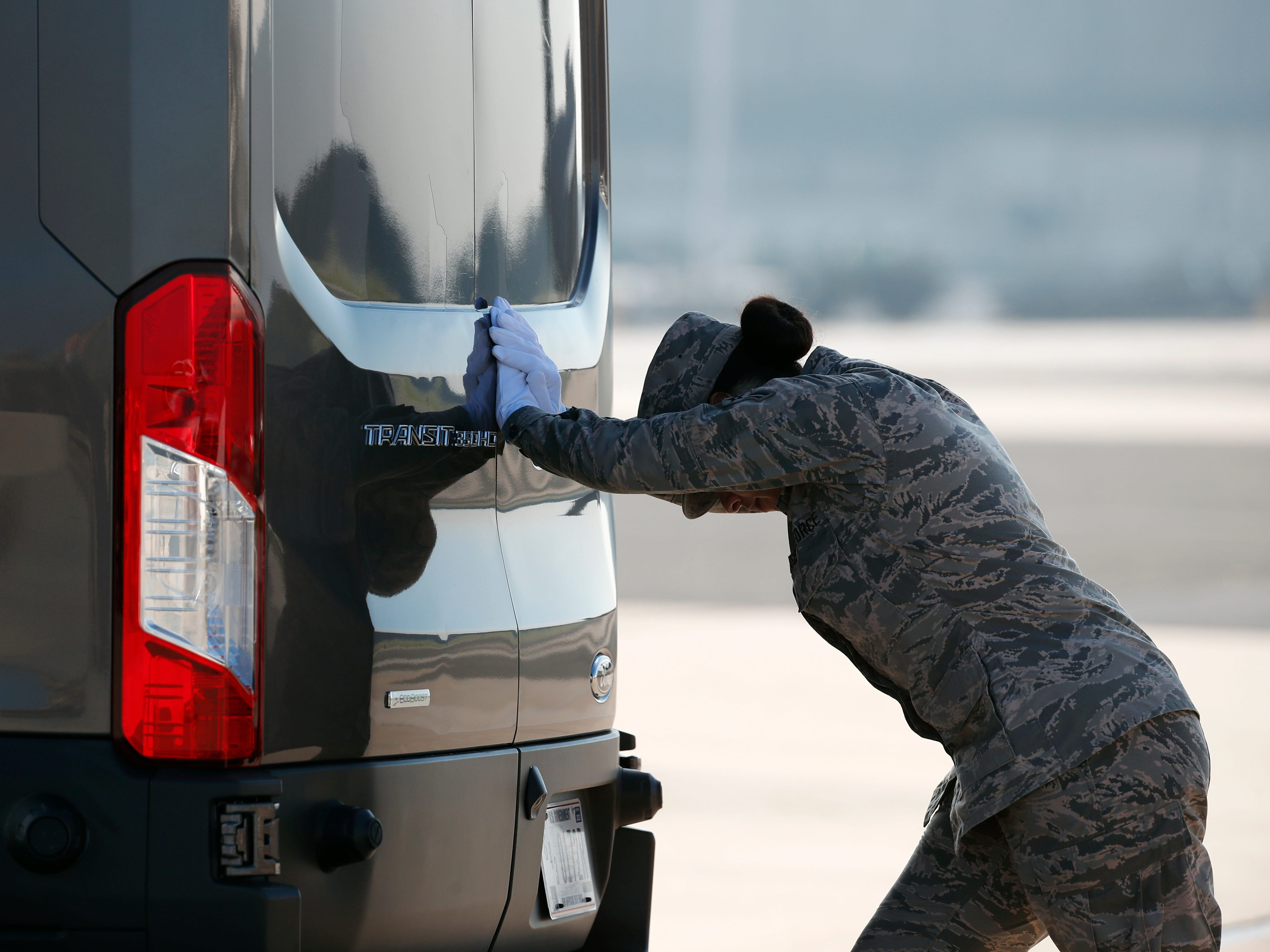 Airman 1st Class Italia Sampson closes the door of a vehicle containing the transfer cases of U.S. Army Command Sgt. Maj. Timothy A. Bolyard, and U.S. Army Staff Sgt. Diobanjo S. San Agustin, at Dover Air Force Base, Del.