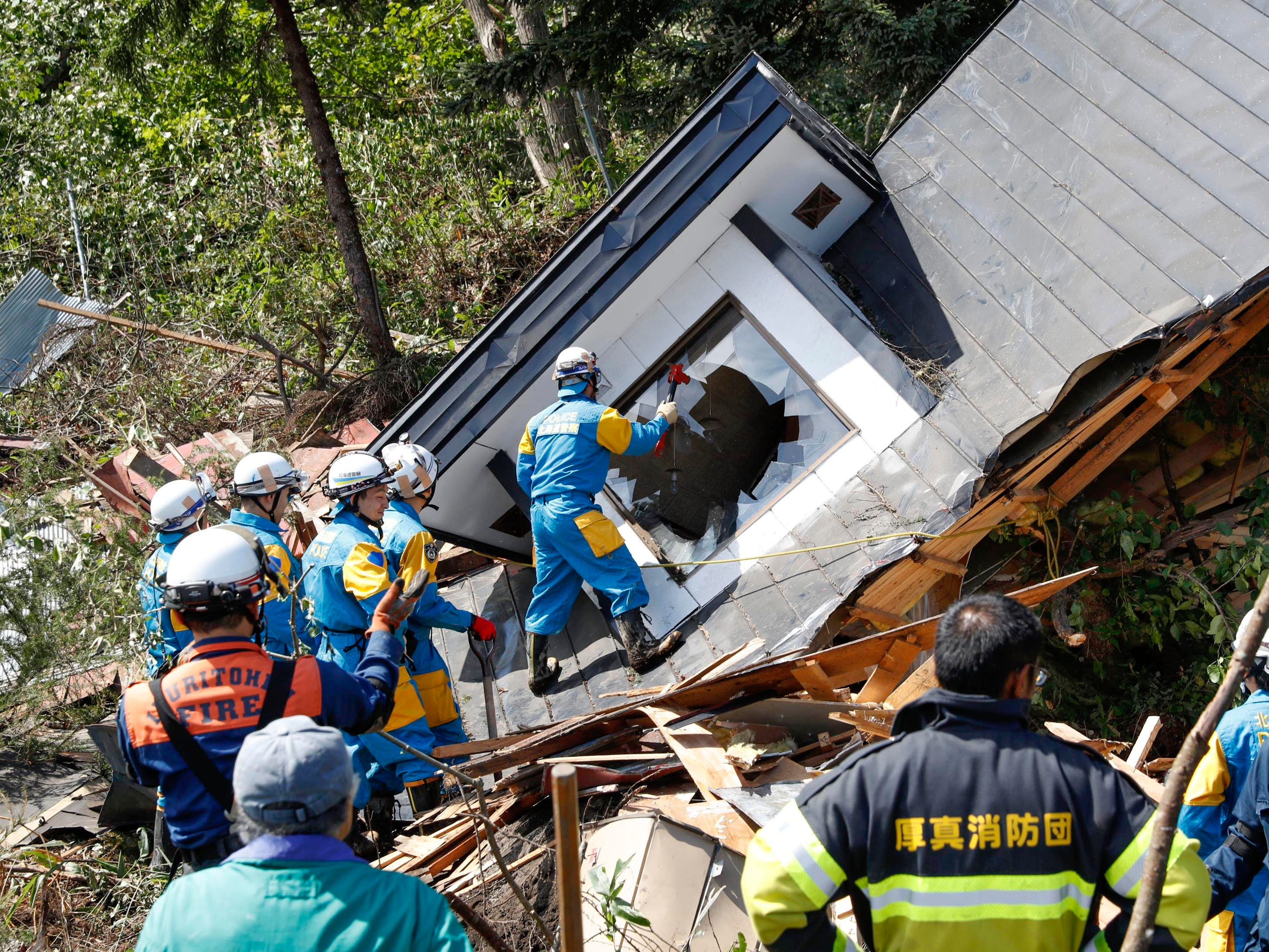 Police, in blue with yellow uniform, search for missing persons around a house destroyed by a landslide after a powerful earthquake in Atsuma town, Hokkaido, northern Japan, Sept. 6, 2018. Several people were reported missing in the nearby the town, where a massive landslide engulfed homes in an avalanche of soil, rocks and timber.