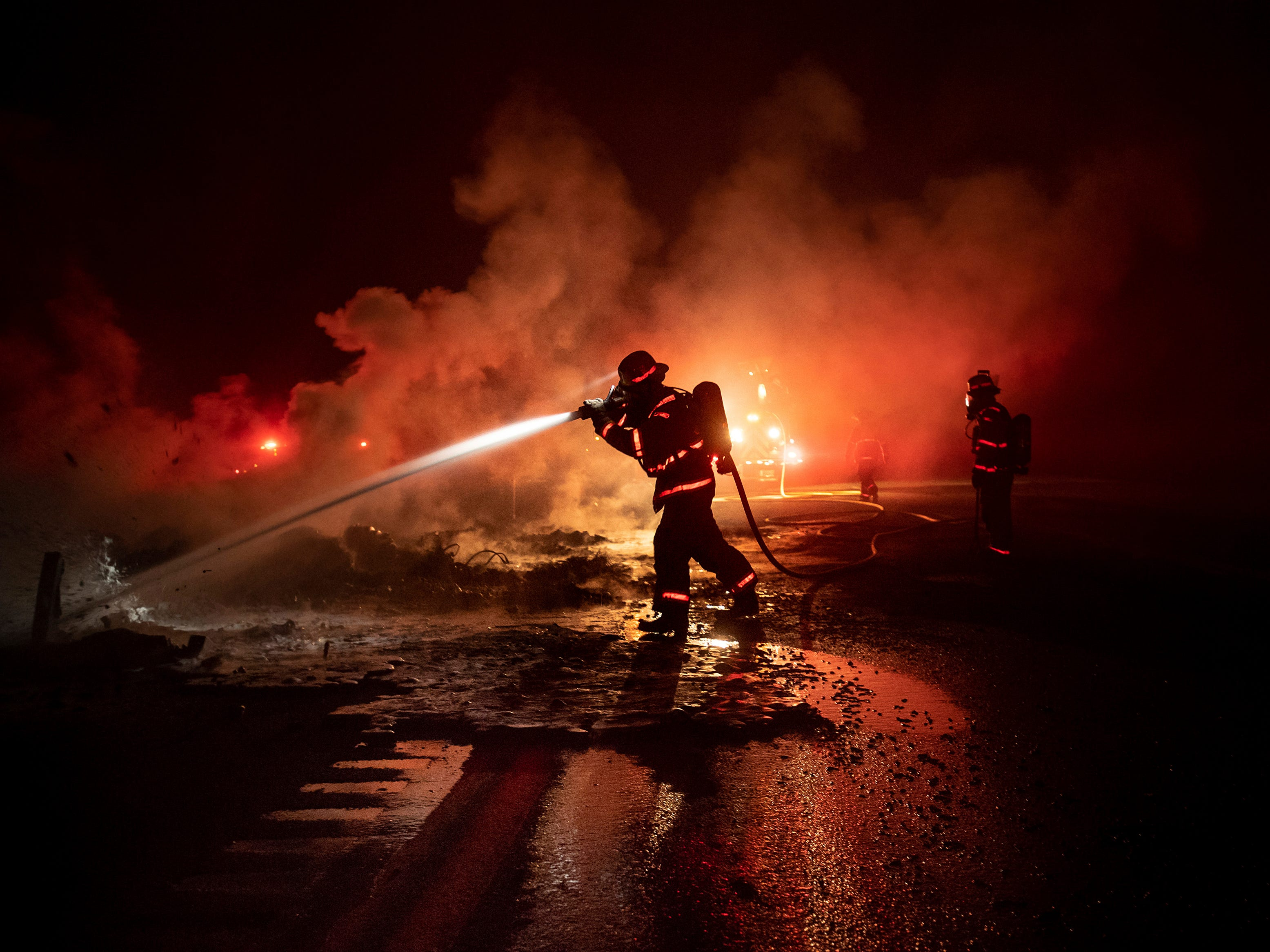 A firefighter sprays the smoldering remains of a vehicle on Interstate 5 as the Delta Fire burns in the Shasta-Trinity National Forest, Calif., Sept. 5, 2018. Parked trucks lined more than two miles of the highway as both directions remained closed to traffic.