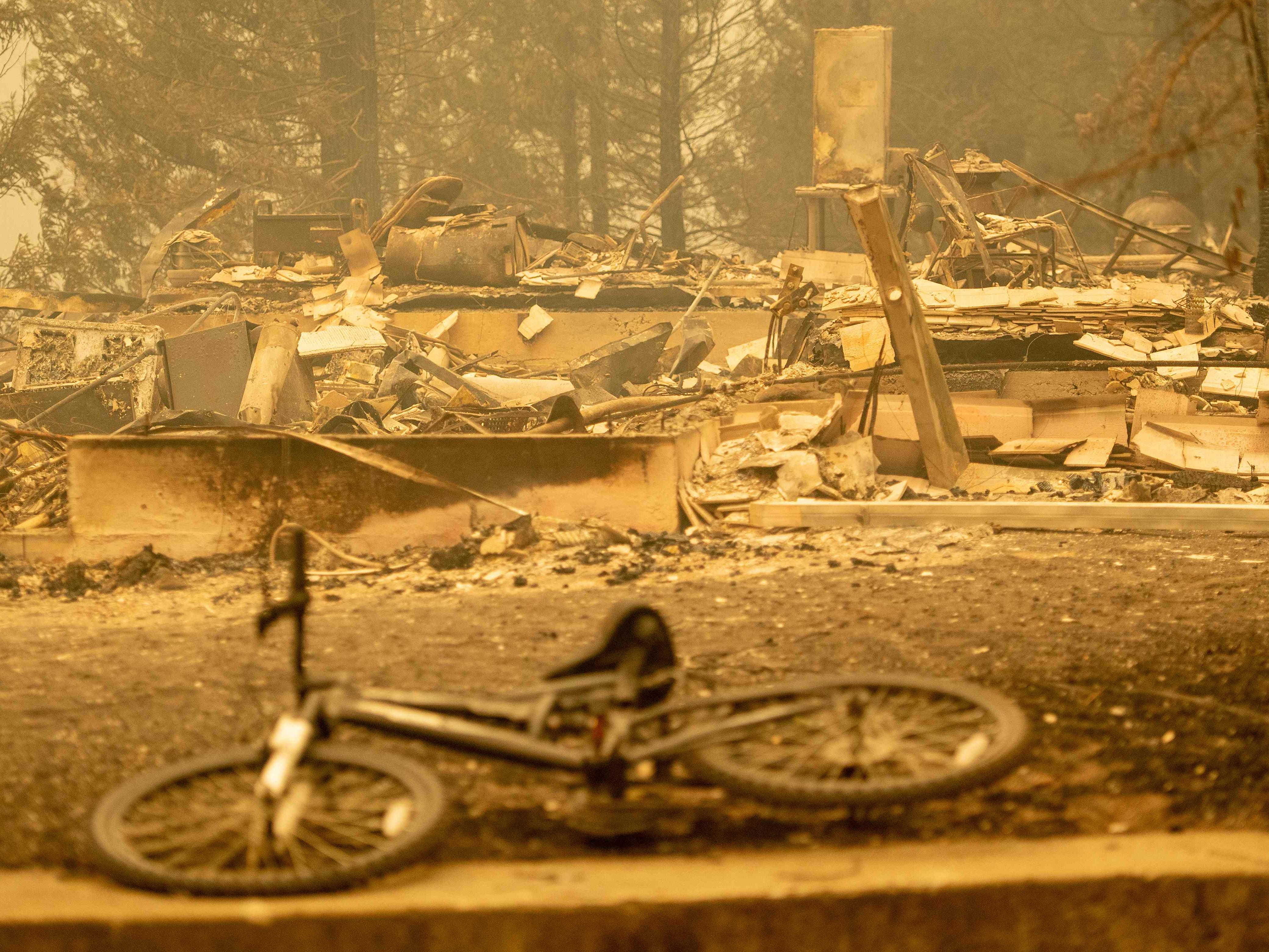 A partially melted bicycle is seen in front of a burned home during the Delta Fire near Delta, California in the Shasta Trinity National Forest on September 6, 2018. (Photo by JOSH EDELSON / AFP)JOSH EDELSON/AFP/Getty Images ORG XMIT: Californi ORIG FILE ID: AFP_18W8D8