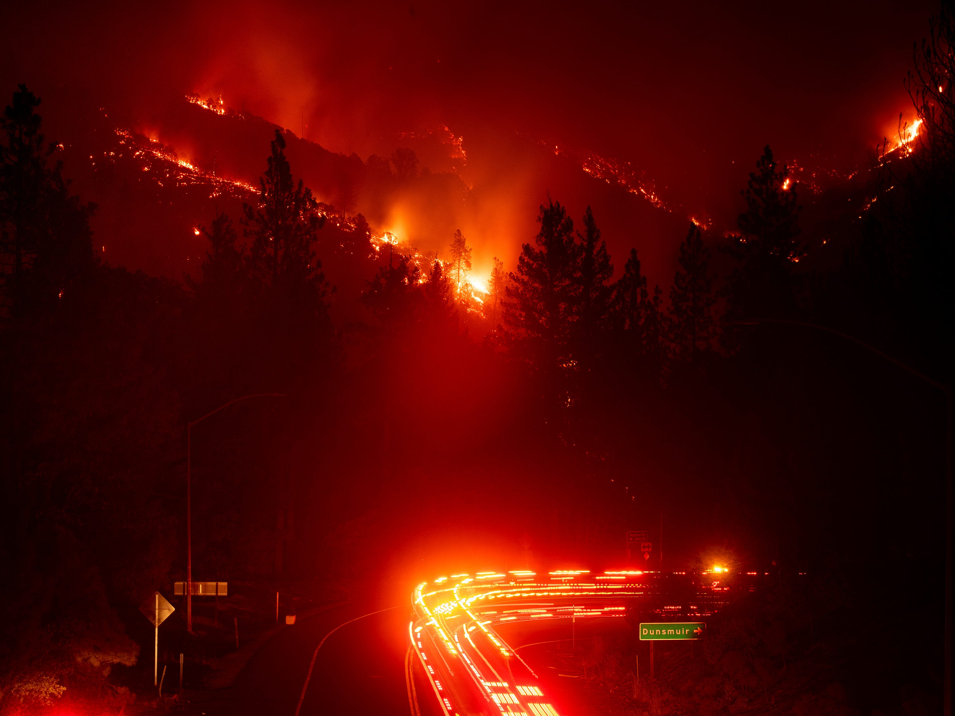 Fire trucks pass the Delta Fire burning in the Shasta-Trinity National Forest, Calif., Sept. 5, 2018. Parked trucks lined more than two miles of Interstate 5 as both directions remained closed to traffic.
