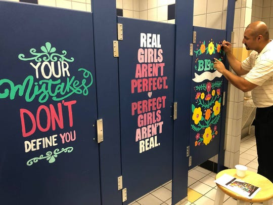 Principal Garcia adds finishing touches to one of the bathroom stalls.