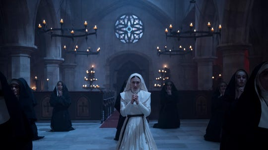 "Sister Irene (Taissa Farmiga) joins a group of women praying to keep evil at bay in ""The Nun."""