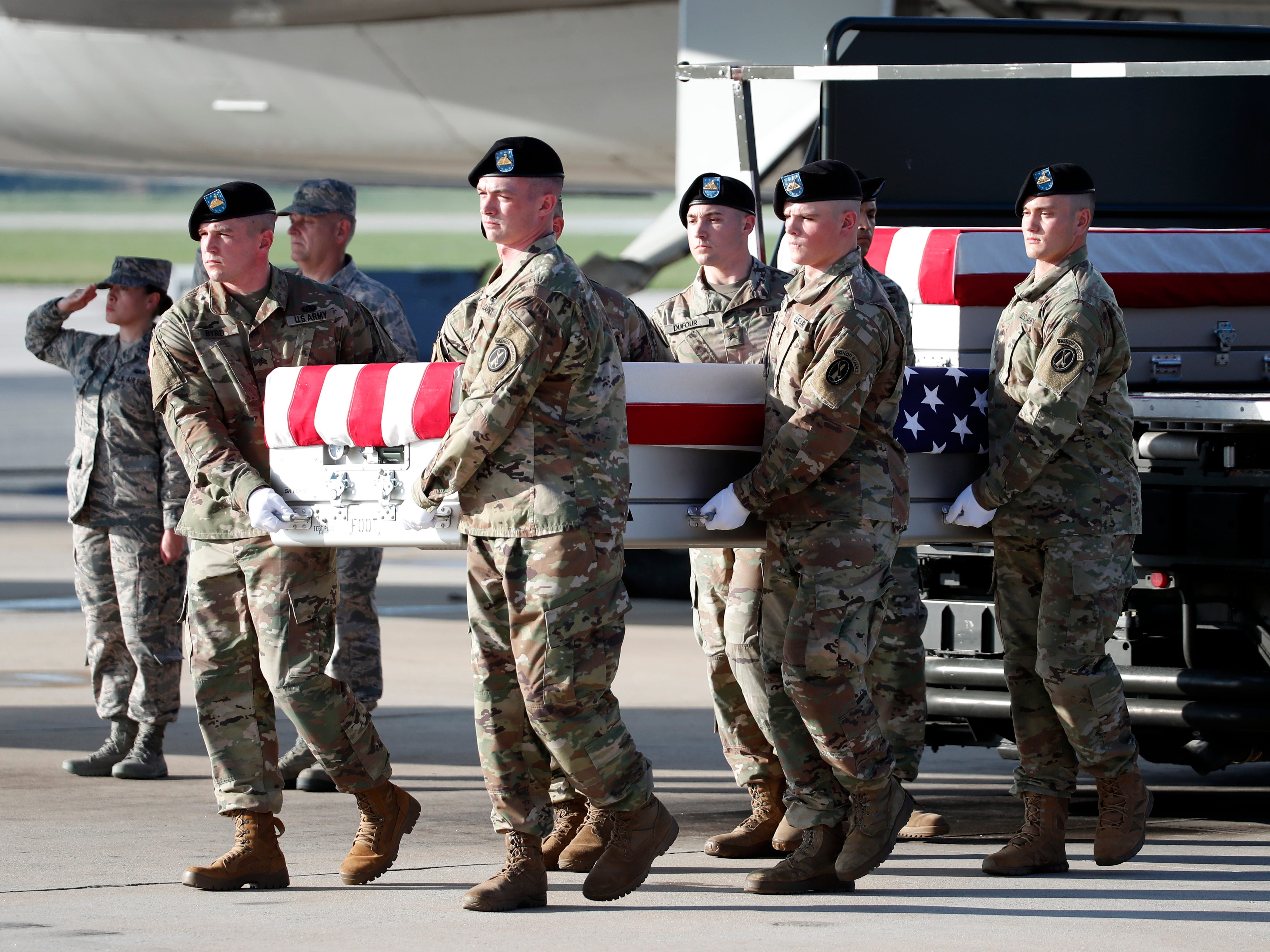 An Army carry team moves a transfer case containing the remains of U.S. Army Command Sgt. Maj. Timothy A. Bolyard, with the remains of U.S. Army Staff Sgt. Diobanjo S. San Agustin, at right, at Dover Air Force Base, Del.