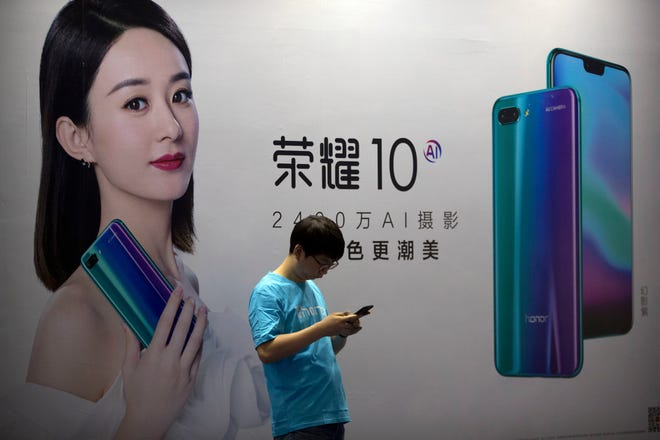 In this April 26, 2018, file photo, a staff member uses his smartphone in front of a billboard for Chinese cellphone maker Honor at the Global Mobile Internet Conference (GMIC) in Beijing.