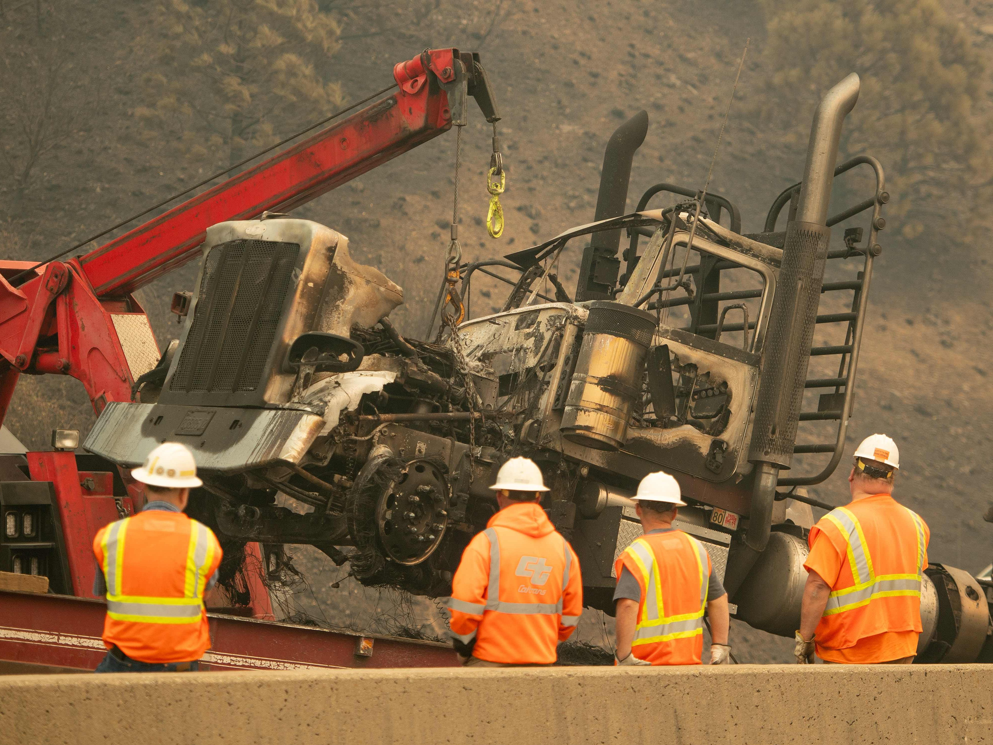 Caltrans workers remove a burned out truck along Interstate 5 during the Delta Fire near Delta, California in the Shasta Trinity National Forest on September 6, 2018. (Photo by JOSH EDELSON / AFP)JOSH EDELSON/AFP/Getty Images ORG XMIT: Californi ORIG FILE ID: AFP_18W7LQ