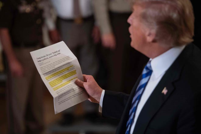 President Donald Trump reads an article praising his administration as he replies to a journalist during a meeting with sheriffs at the White House on Sept. 5, 2018.