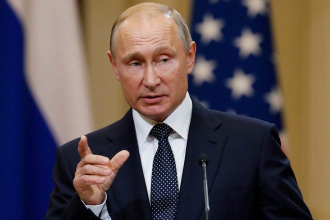 In this photo taken on Monday, July 16, 2018, Russian President Vladimir Putin gestures while speaking at the joint press conference with U.S. President Donald Trump after their meeting at the Presidential Palace in Helsinki, Finland.