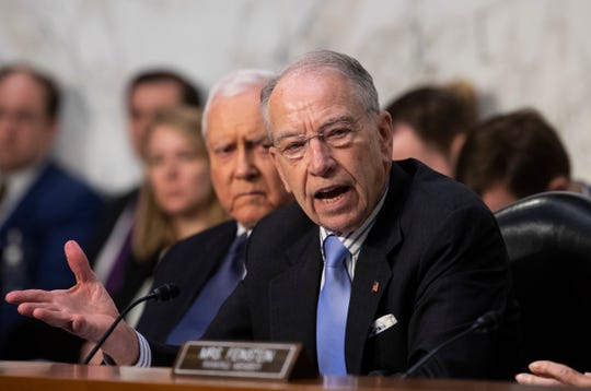 Senate Judiciary Committee Chairman Chuck Grassley, R-Iowa, joined at left by Sen. Orrin Hatch, R-Utah, deals with objections from Democratic members of the panel as Supreme Court nominee Brett Kavanaugh waits to testify before on the third day of his confirmation hearing, on Capitol Hill in Washington, Sept. 6, 2018.