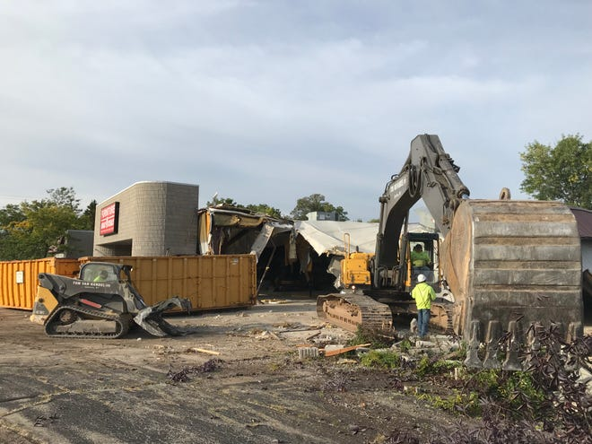 Workers demolish a portion of the former Furniture Deals & Steals building.