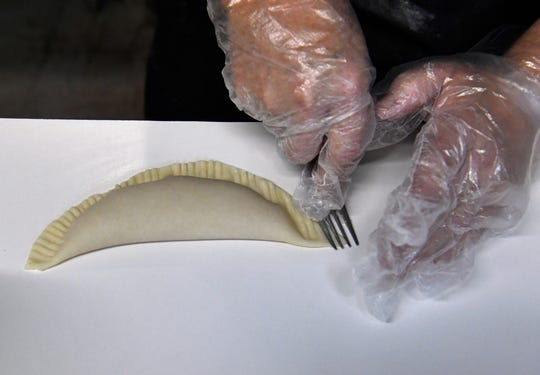 Charlotte Herman uses a fork to close a soon-to-be fried pie. She is the owner of Unperfect Fried Pies in Stamford.