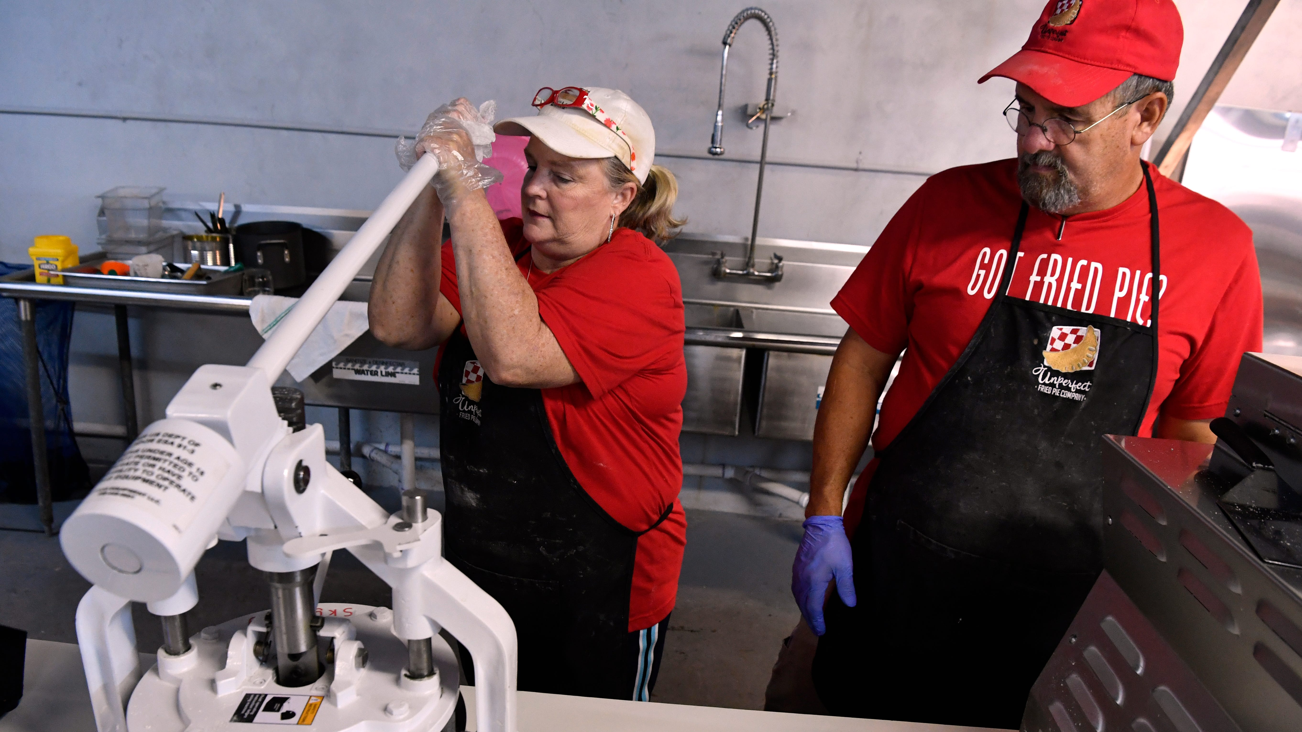 Charlotte Herman uses a machine to cut her pie dough into separate blocks while her husband Burney watches August 30, 2018. She is the owner of Unperfect Fried Pies in Stamford.
