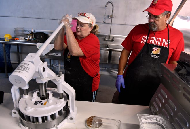 Charlotte Herman uses a machine to cut her pie dough into separate blocks while her husband Burney watches Aug. 30. She is the owner of Unperfect Fried Pies in Stamford.