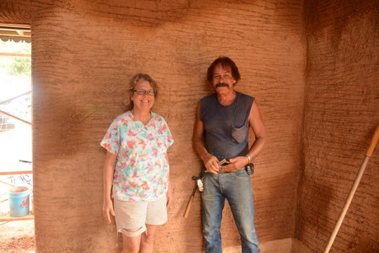 Homeowner Elizabeth Pantzer and builder Edward Roberts stand in front of one of the clay, sand and straw covered walls.