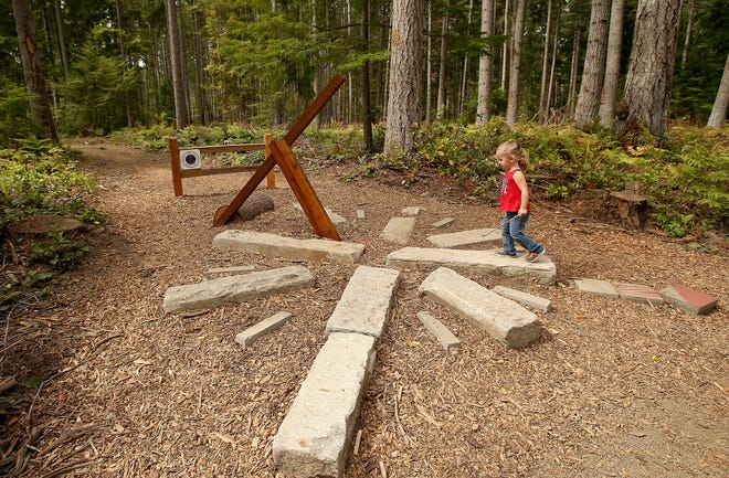 Maylee Fuchs, 2, walks along a compass/sundial fixture on the new Explorer Trail at South Kitsap Regional Park in Port Orchard on Friday.