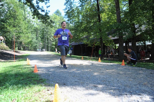 Dennis Gregory crosses the finish line of the Gateway 5K at Camp Grier in Old Fort on Sept. 3. Gregory was one of a group of runners who participated in an 11-week training program for people interested in trail running.