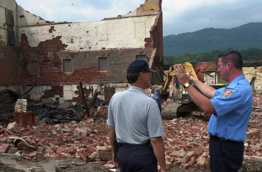 Arson investigator Buddy Thompson. left, and Swannanoa fire chief Anthony Penland discuss knocking down an unstable wall before investigators can examine the area of the Beacon building in 2003.