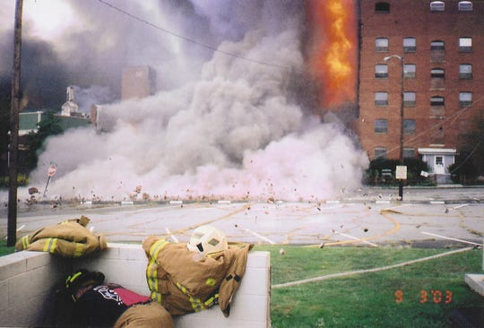 A firefighter takes cover in front of the Swannanoa Fire Department as an exterior wall of the Beacon Manufacturing building collapses during the 2003 fire, scattering bricks for blocks.